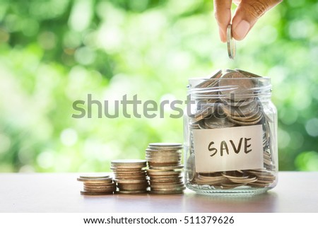 Hand putting Coins in glass jar for money saving financial concept