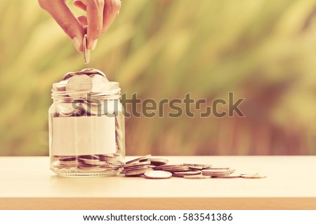 Hand putting Coins in glass jar with blank label for giving and donation concept
