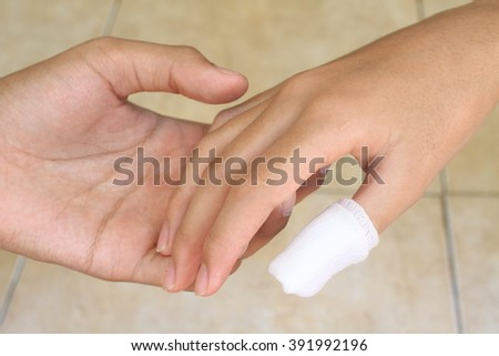 hand putting elastic tape on hand hurt