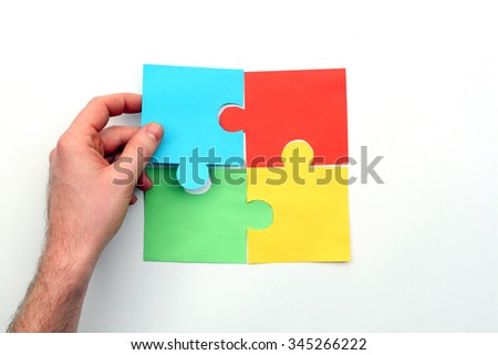 Hand putting last puzzle piece.