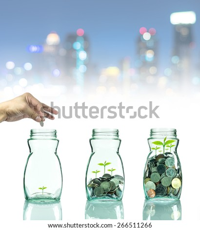 Hand putting mix coins and seed in clear bottle on cityscape photo blurred bokeh background,Business investment growth concept - stock photo