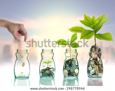 Hand putting mix coins and seed in clear bottle on cityscape photo blurred cityscape background,Business investment growth concept - stock photo