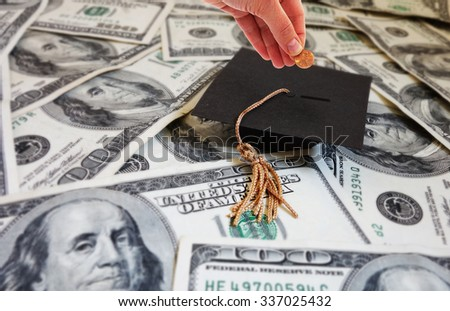 Hand putting money into a graduation cap -- student loan repayment or college savings concept                                - stock photo
