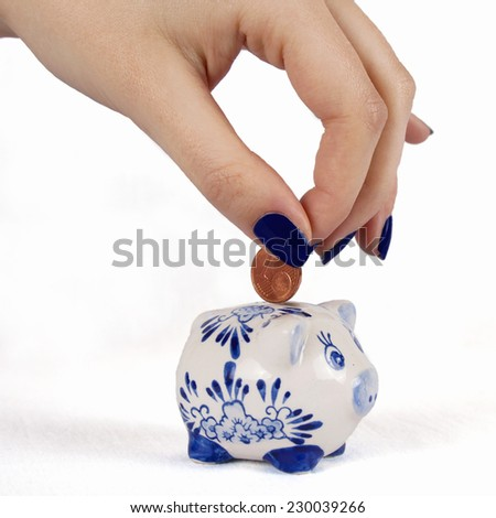 Hand putting one cent into a small blue piggy bank - stock photo