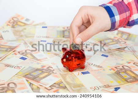 Hand putting one euro coin in red piggy bank on euro bills - stock photo