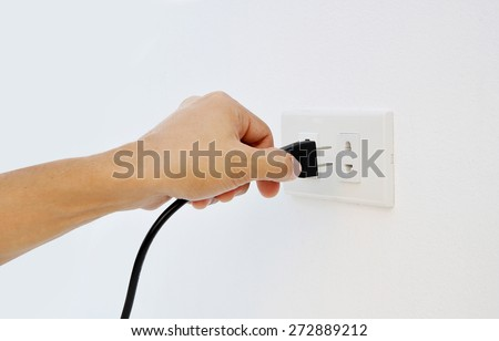 Hand Putting Plug Into Electricity Socket on clean cement plaster wall background