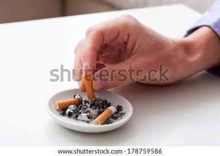 Hand putting the cigarette on an ashtray - stock photo