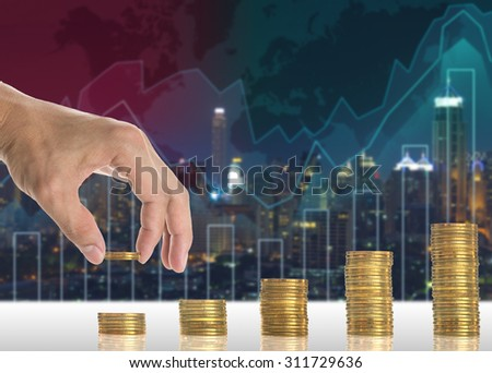 Hand putting the gold coins on the stack of golden coins on Trading graph on the cityscape blurred background, Business financial concept - stock photo