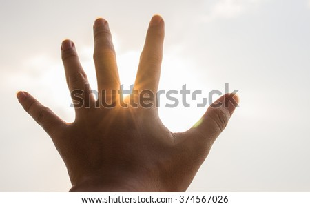Hand ray silhouette on the sun light - stock photo
