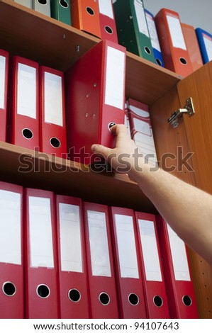 hand reaching down to the binder - stock photo