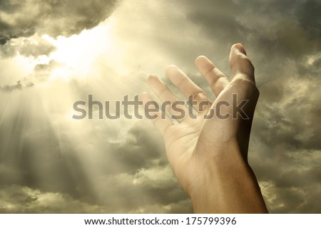 Hand reaching for a ray of light on the sky - stock photo