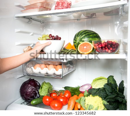 Hand Reaching for Green Apple in Refrigerator Full of Healthy Food Options