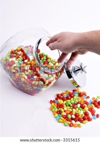 hand reaching into open jar of colorful jelly beans - stock photo