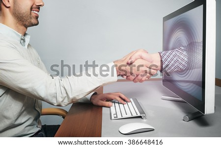 Hand reaching out from screen  to shake hand - stock photo