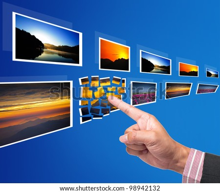 Hand reaching point to images - stock photo