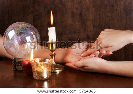 Hand reading the lines in the hand of another woman - stock photo
