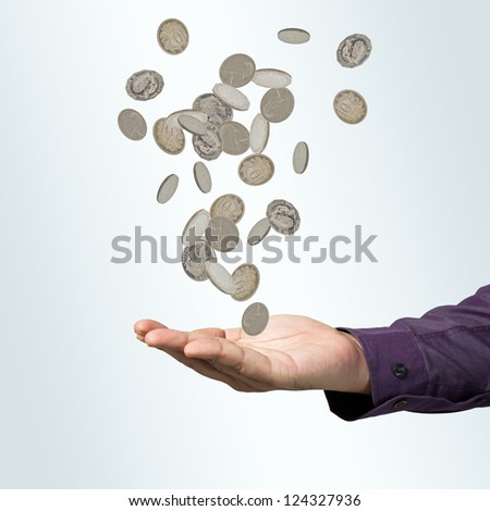 Hand receiving many falling coins - stock photo