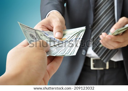 Hand receiving money from businessman - United States dollar (USD) bills - stock photo