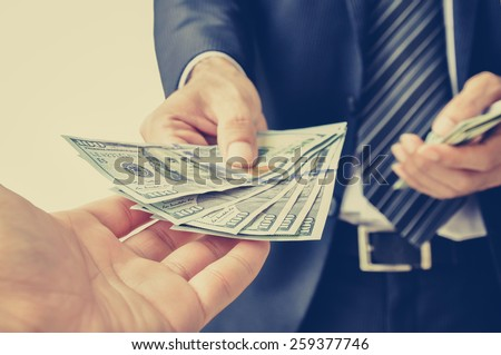 Hand receiving money, US dollar (USD) bills, from businessman hand - vintage style color effect - stock photo