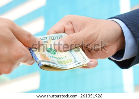 Hand receiving money, US dollars, from businessman - bribery concept - stock photo
