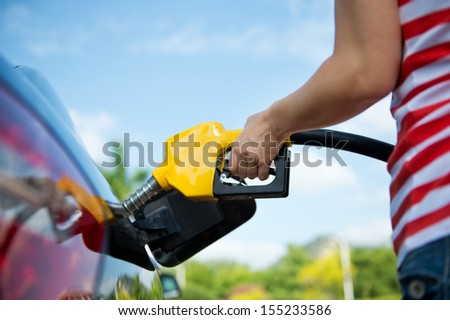 Hand refilling the car with fuel. - stock photo