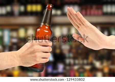 hand reject a bottle of beer in the bar - stock photo