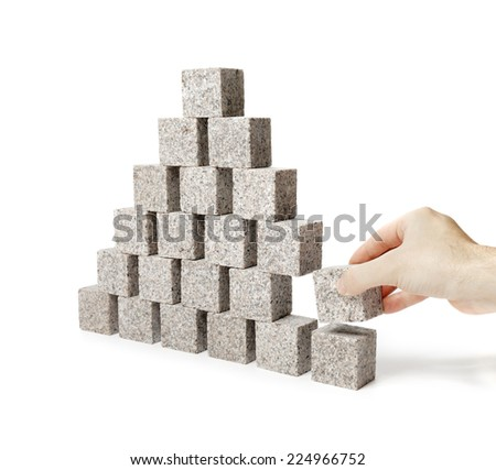 Hand removing one block of a pyramid made of small granite rock blocks. - stock photo