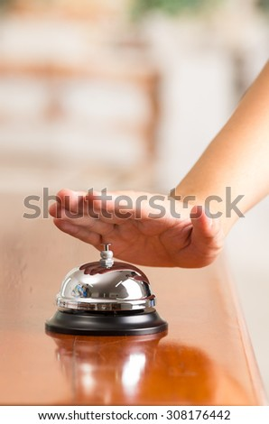 hand ringing hotel bell in reception desk close up selective focus - stock photo
