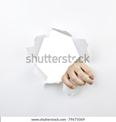 Hand ripping a hole with torn edges in white paper - stock photo