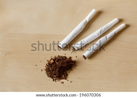 Hand rolled cigarettes and tobacco on a wooden table - stock photo