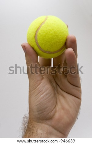 Hand's man holding a yellow ball of tennis; white background