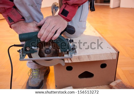 Hand saw cutting the timber - stock photo