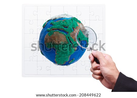 hand searching globe by magnifying glass on jigsaw concept ecology isolate on white background with clipping path  - stock photo