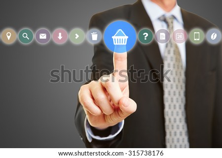 Hand selecting shopping cart on touchscreen with many different symbols - stock photo