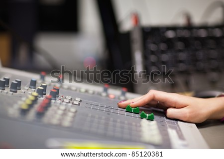Hand setting the sound in a studio - stock photo