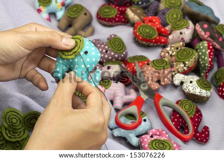Hand sewing a elephant cloth dolls - stock photo