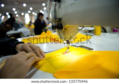 Hand sewing a material on a machine. - stock photo
