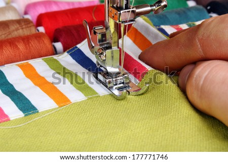 Hand sewing on a machine and item of clothing material - stock photo