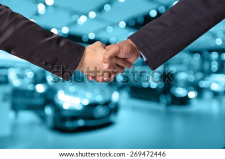 Hand shake between a businessman and a businesswoman on abstract blurred photo of motor show background