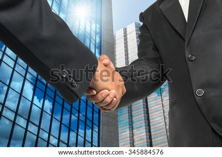 Hand shake between businessman on Modern glass building background - stock photo