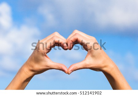 Hand shaped heart against sky background.