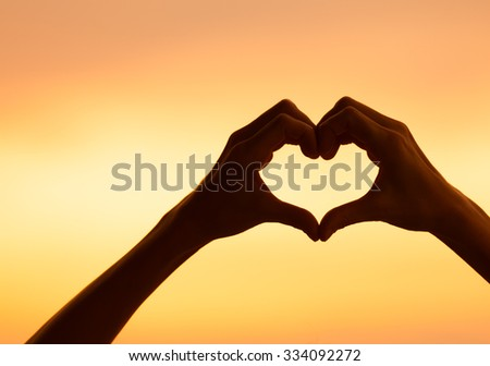 Hand shaped heart in the sky. - stock photo