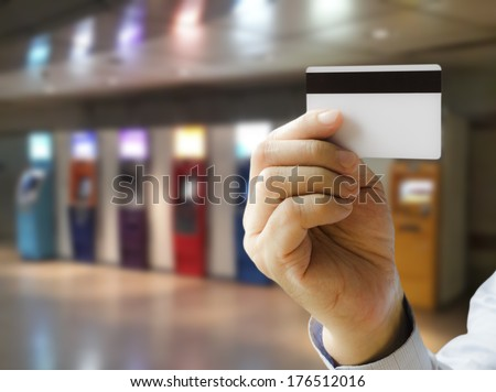 Hand show credit card with ATM machines as a backdrop - stock photo