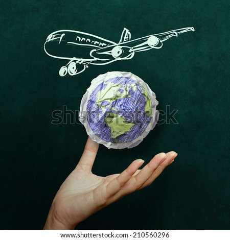hand showing airplane with crumpled world paper symbol as concept on blackboard - stock photo