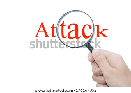 Hand Showing attack Word Through Magnifying Glass  - stock photo