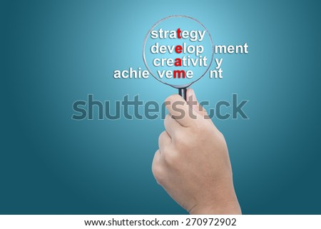 Hand Showing Business Team,strategy,development ,creativity,achievement Word Through Magnifying Glass