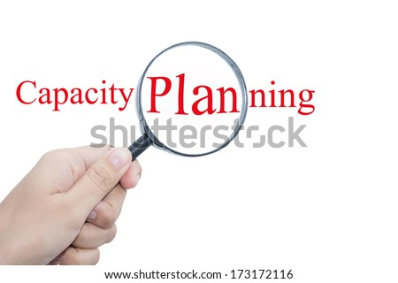 Hand Showing Capacity Planning Word Through Magnifying Glass  - stock photo