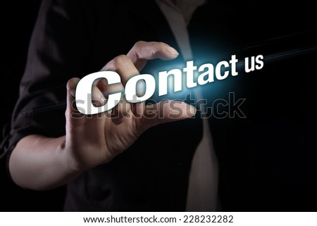 Hand showing contact us text on the virtual screen - stock photo
