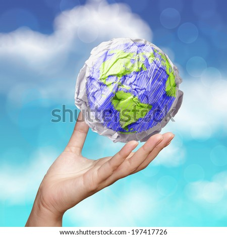 hand showing crumpled world paper symbol as concept on blue sky background  - stock photo