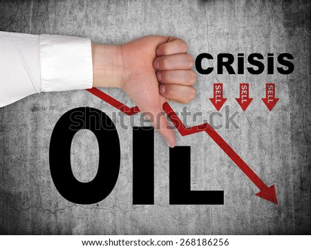 hand showing dislike sign and drawing falling oil chart on wall - stock photo